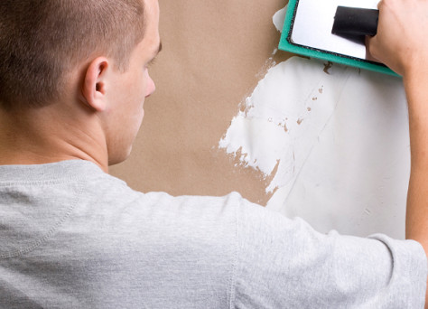 Caucasian worker plastering a brown wall with white plaster.